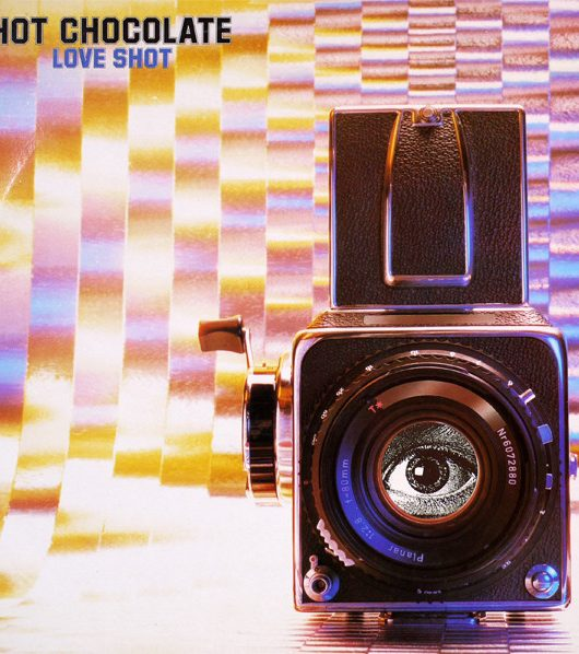 An image of Hot Chocolate's studio album Love Shot. This album cover features an old analogue camera with a black and white image of an eye where the lens should be. The background is a shiny, psychedelic print with lettering in the top left-hand corner reading 'Hot Chocolate' in black block letters and 'Love Shot' in identical smaller violet letters underneath.